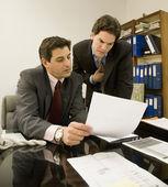 Hispanic businessmen looking at paperwork — Stock Photo