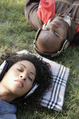African couple listening to headphones in grass — Stock Photo