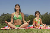 Mother and daughter meditating together — Stock Photo