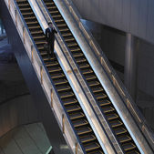 Businessman with briefcase on escalator — Stock Photo