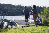 Couple carrying canoe out to lake — Stock Photo