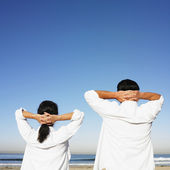 Hispanic couple with hands behind head at beach — Stock Photo