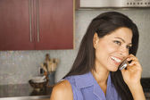 Hispanic woman talking on cell phone in kitchen — Stock Photo