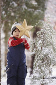 Boy with Christmas star and snowy tree in forest — Stock Photo