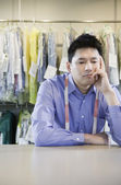 Bored Asian dry cleaner — Stockfoto