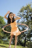 Hispanic girl playing with hula hoop outdoors — Stock Photo