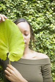 Woman holding leaf in front of face outdoors — Stock Photo
