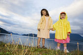 Portrait of sisters holding hands at lake — Stock Photo