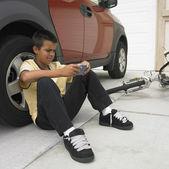 Niño jugando videojuegos mientras que se inclina contra el vehículo — Foto de Stock