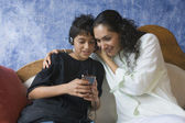 Hispanic mother and son listening to mp3 player — Stock Photo