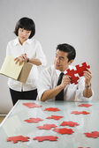 Asian woman timing man putting together puzzle — Stock Photo