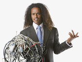 Businessman holding tangled computer cords — Stock Photo