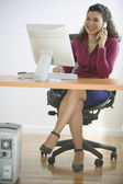 Businesswoman talking on phone while sitting at desk with computer — Stock Photo