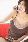 Asian woman on cell phone laughing — Stock Photo