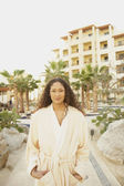 Hispanic woman in bathrobe outdoors at resort hotel — Stock Photo