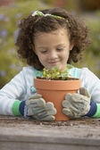 Girl planting flowers in pot — Stock Photo