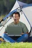 Portrait of man on laptop outside of tent — Stock Photo