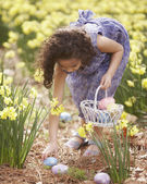 Girl picking up Easter eggs — Stock Photo