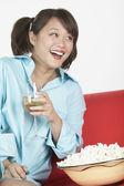 Asian woman wearing man's shirt on sofa with wine — Stock Photo