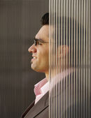 Businessman partially obscured by glass wall — Stock Photo
