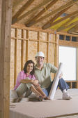 Couple with blueprints on construction site — Stock Photo