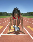 Female track athlete poised at starting line — Stock Photo