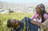 African couple sitting in grass on hill above city — Стоковое фото