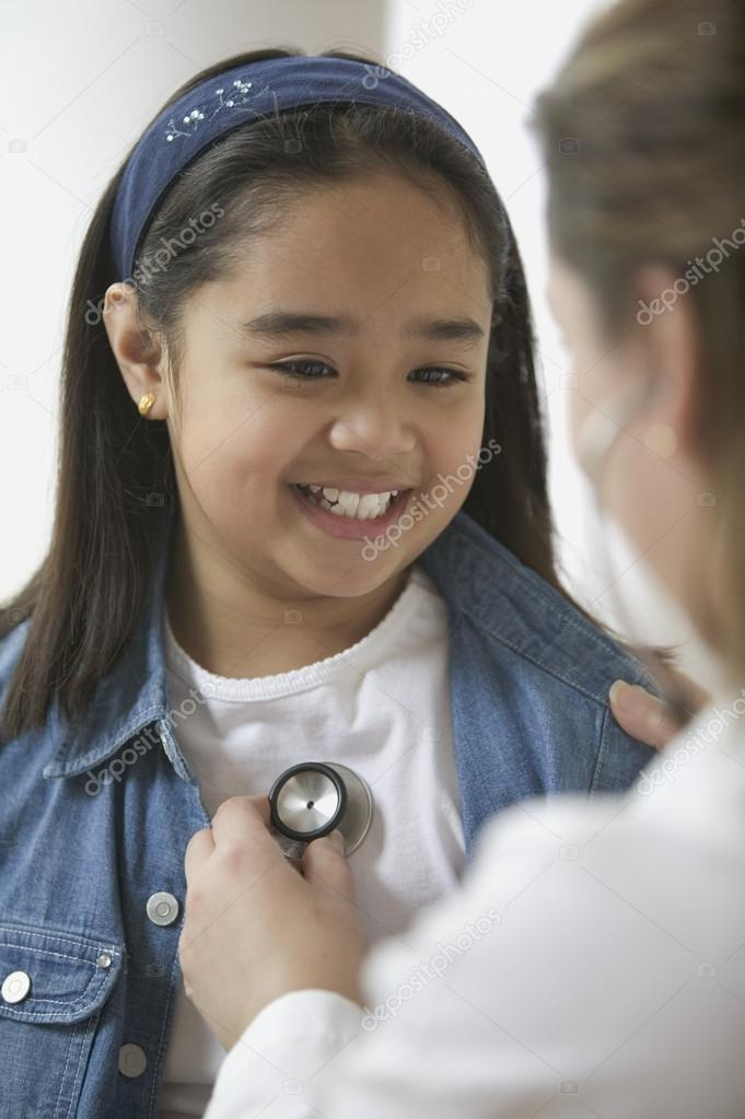 Female doctor listening to young girl's heartbeat — Stock Photo #13220899
