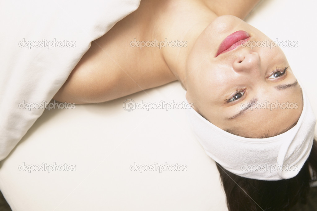 Young woman laying underneath a towel  Stock Photo #13220952