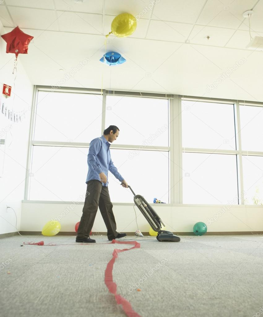 Man vacuuming after office party  Stock Photo #13221128