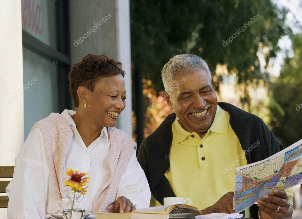 Senior couple looking at map while sitting at table  Stock Photo #13221169