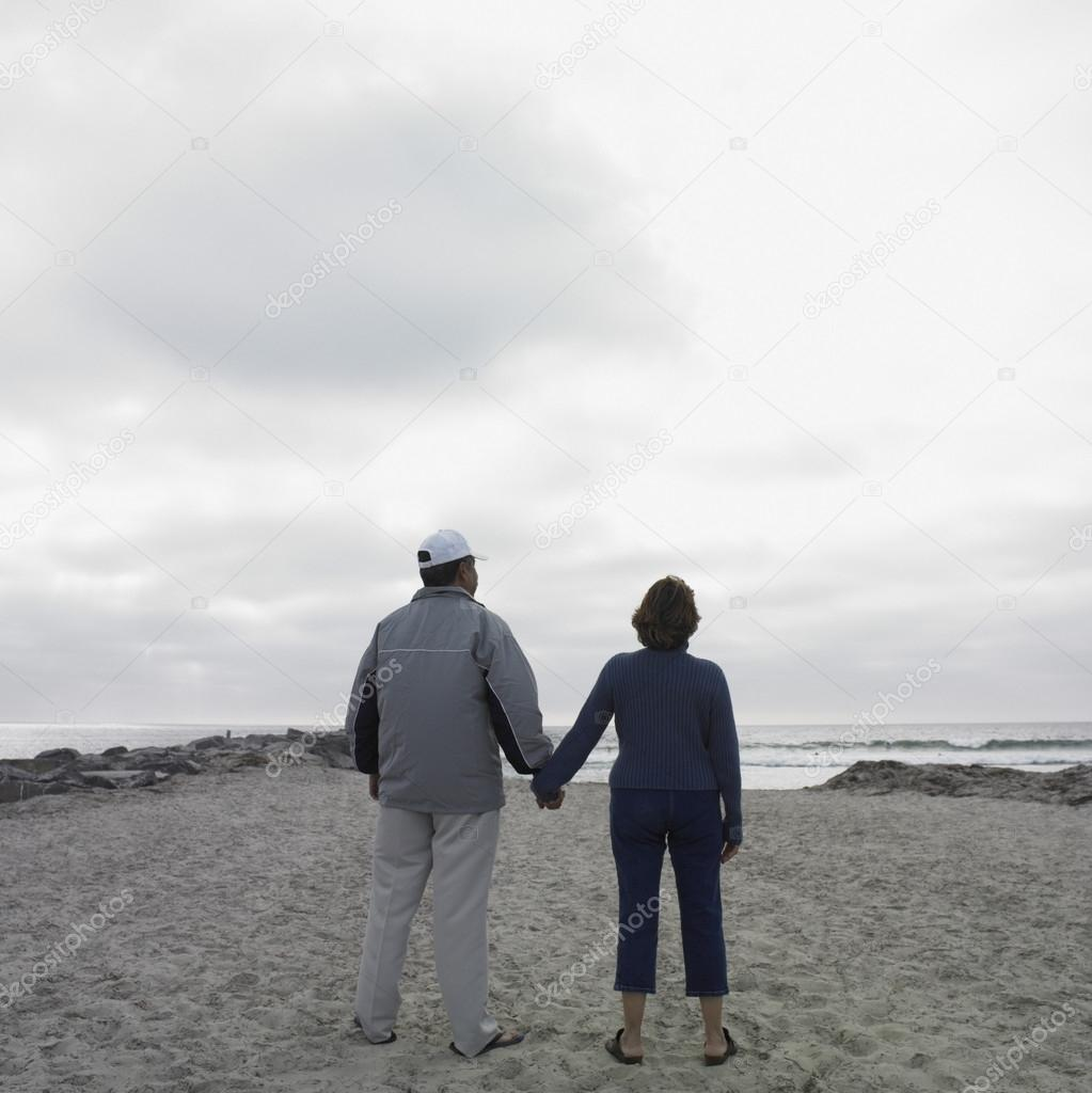 Couple holding hands on the beach — Stock Photo #13222086