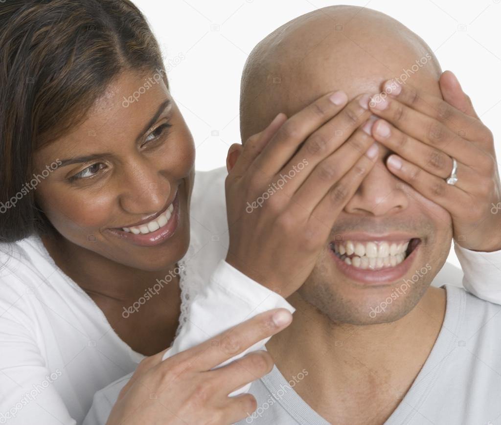 Woman with hands over man's eyes — Stock Photo #13223292