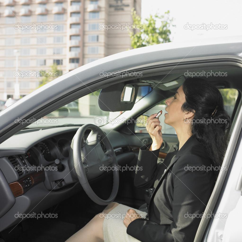 Businesswoman applying makeup inside car — Stock Photo ...