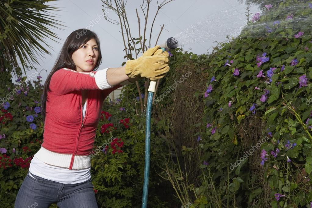 Woman spraying water from hose — Stock Photo #13228200
