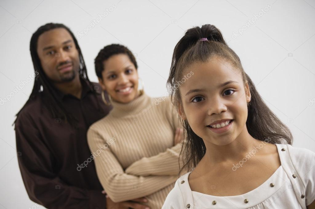 Studio shot of African girl smiling with parents in background — Stock Photo #13228344
