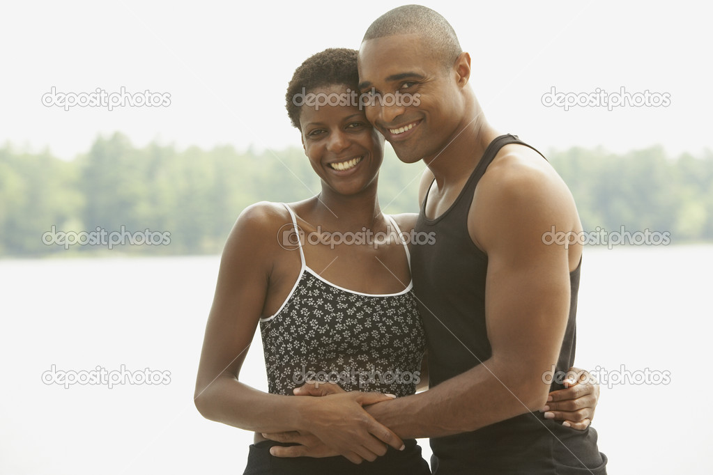 African couple smiling and hugging outdoors — Stock Photo #13228348