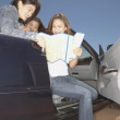 Friends in convertible looking at map — Stock Photo #13230213