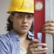 Woman construction worker in hard hat reading level measurements — Stock Photo #13230840