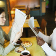 Couple reading newspaper in restaurant — Stock Photo