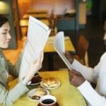 Couple reading newspaper in restaurant — Stock Photo