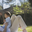 Baby sitting on mother outdoors — Stock Photo #13230052