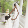 African American bride dancing with flower girl - Stockfoto
