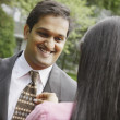 Indian woman adjusting husband's necktie - Stock Photo
