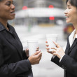 Businesswomen talking while drinking coffee — Stock Photo