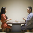 Asian couple kneeling having tea — Stock Photo