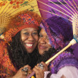 Two senior African women holding parasols - Stock Photo
