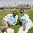 Senior African couple laying in grass smiling with cityscape in background — Stock Photo