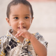 Young boy with finger over mouth — Stok fotoğraf