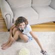 Hispanic woman eating popcorn and changing channel with remote control — Stok fotoğraf